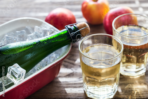 Tableau sur Toile Bottle and two glasses of cider on the wooden background
