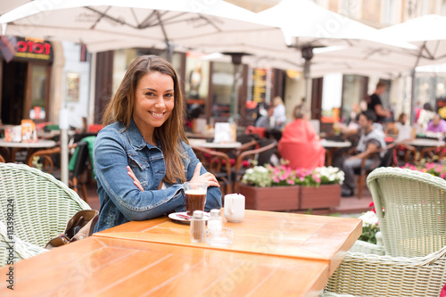 Foto  a portrait of a young woman sitting outside a restaurant smileing