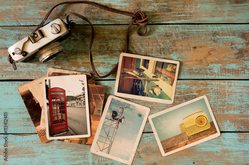 Obraz Retro technology instant photo album on wood table. paper photo of vintage camera - vintage and retro style - fototapety do salonu