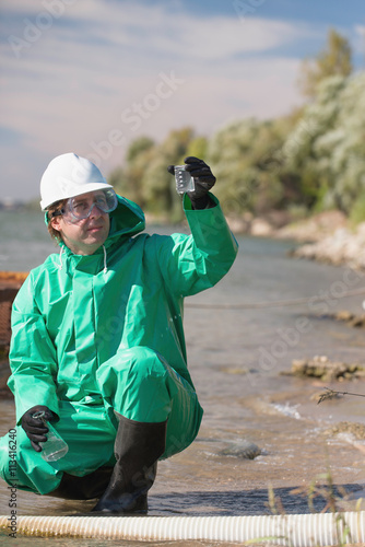 Fotografie, Obraz  Environmentalist looking at sample of polluted water