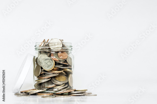Fotografía  Glass jar full of coins, with copy space on white background