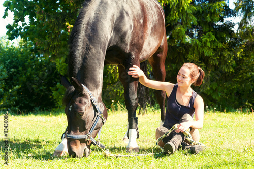 Young woman equestrian sitting close to her horse on grass