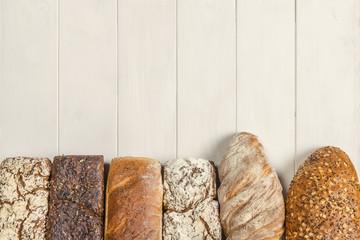 Rząd smacznych chlebów jasnych i ciemnych z pełnego ziarna - tło kompozycja piekarnicza