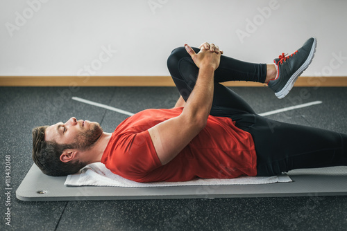 healthy man stretching leg before gym workout Fototapeta