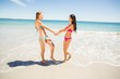 Female friends holding hands on beach