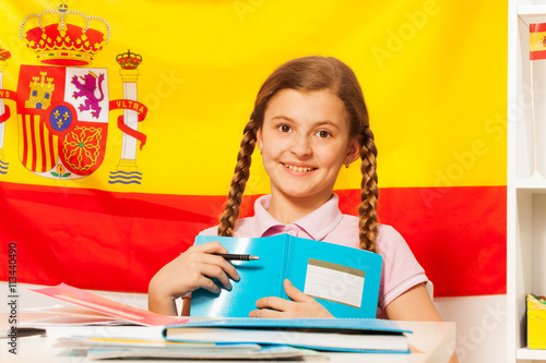 Foto  Cute girl with book and the Spanish flag behind
