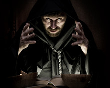 Necromancer Casts Spells From Thick Ancient Book By Candlelight On A Dark Background