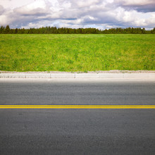 Empty Highway. Roadside With Green Grass