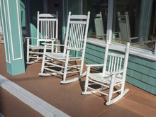 Row Of Hand Crafted Adirondack Rocking Chairs On Front Porch Of A Store Invite Husbands To Sit And Chat For A Short Time Waiting For Their Wives