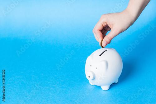 Fotografía  Inserting a coin into a piggy bank