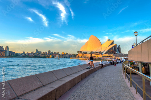 Photo Stands Sydney Tourists walking next to opera bar in front of Sydney Opera Hous