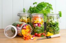 Salad In Glass Storage Jars. One Spilling Contents.