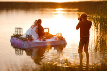 Wedding Photographer In Action, Taking A Picture Of The Bride And Groom Sitting On The Raft. Summer, Sunset