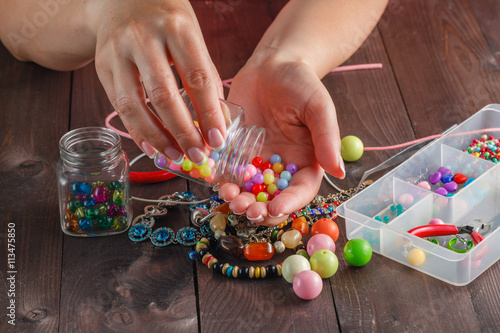Fotografie, Obraz Pair of hands and pliers assembling a bead necklace.