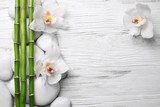 Fototapeta Orchid - Beautiful spa composition with bamboo on light wooden background