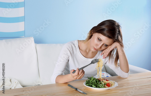 Fotografie, Tablou Young depressed girl with eating disorder at wooden table