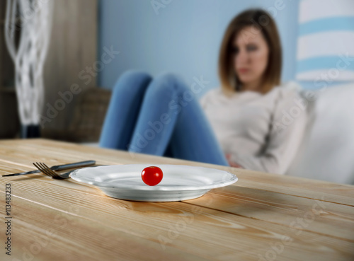 Photo Young depressed girl with eating disorder at wooden table