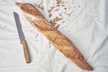 Baguette Bread And Knife On White Table Cloth - Top View