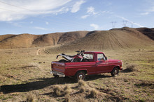 Motorcycle In Pick-up Truck On Arid Landscape Against Sky