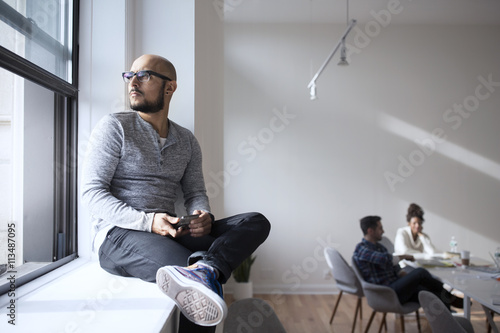 Thoughtful businessman sitting on window with colleagues in background