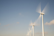 Low Angle View Of Wind Turbines In Motion Against Sky
