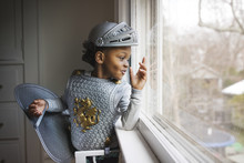 Little Boy Dressed Up In Armor Costume Looking Out Through Window At Home