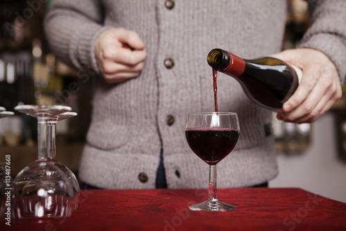 Mid section of sommelier pouring red wine in wine glass in the shop