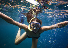 Portrait Of Young Woman Wearing Goggles Snorkeling Undersea