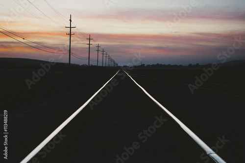 Railroad Railroad tracks on silhouette landscape against cloudy sky during sunset