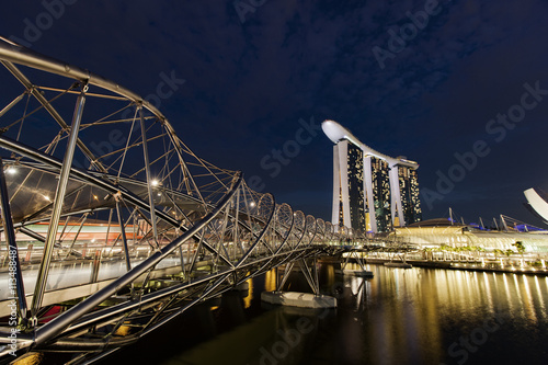 Helix Bridge over Singapore River by Marina Bay Sands against sky at night