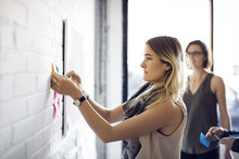 Businesswoman Sticking Notes On Wall At Creative Office