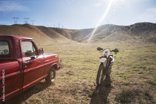 Motorcycle and pick-up truck on arid landscape against sky Poster