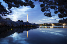 Washington Monument By Lake Against Cloudy Sky At Dusk