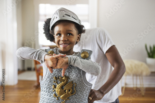 Father assisting cheerful boy in getting dressed as armor at home Poster
