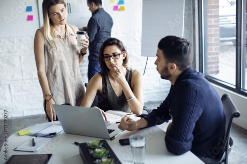 Business people using laptop while discussing at creative office