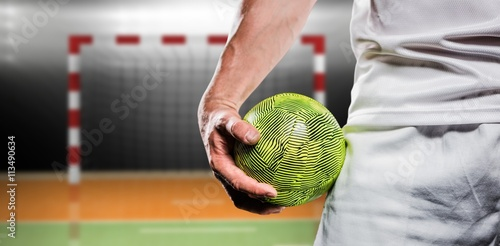 Fotografia, Obraz Sportsman holding a ball against digital image of handball goal