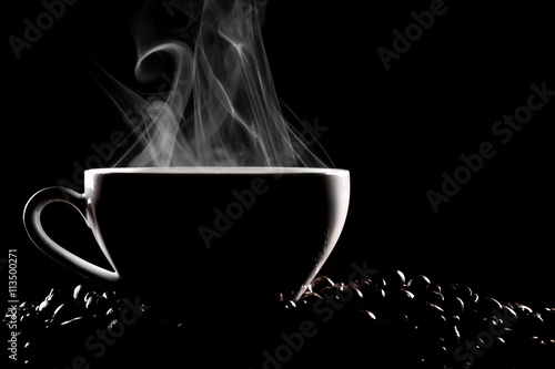 Door stickers Cafe Steaming coffee cup and coffee beans in studio play of light and shadow on black background.
