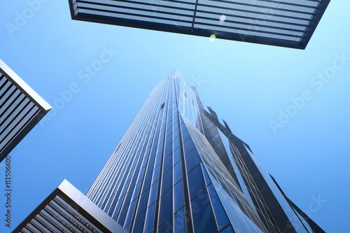 In de dag Tunnel High rise office tower with blue windows and blue sky. Modern building