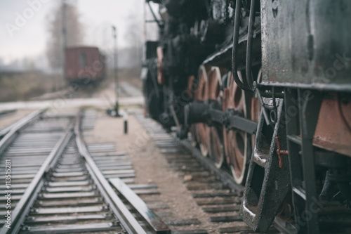 Vintage steam train and the track at the railway station on a cl плакат