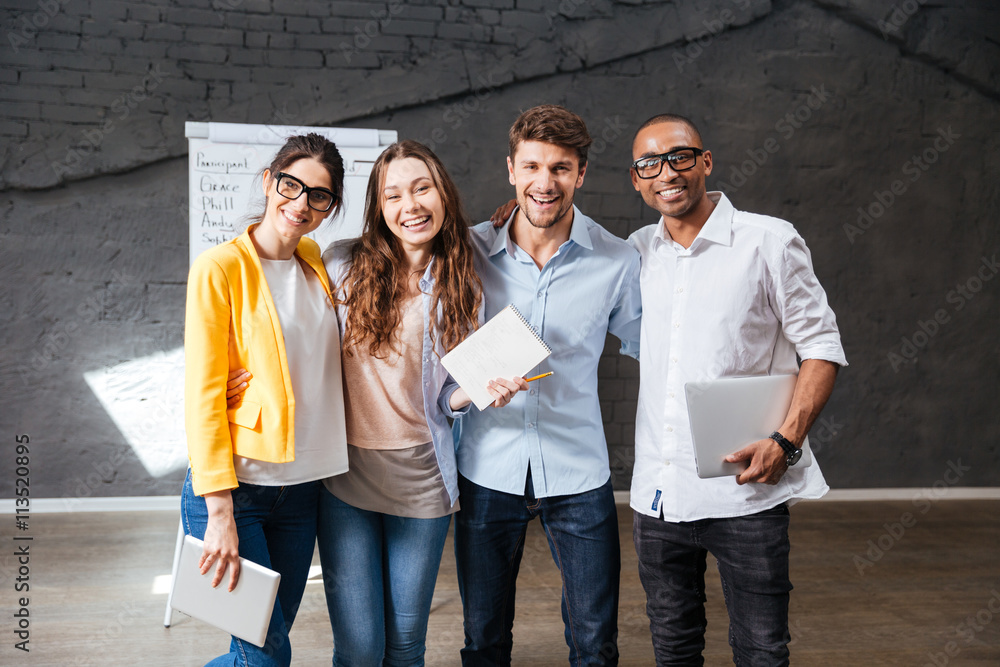 Fototapeta Multiethnic group of happy young business people standing in office