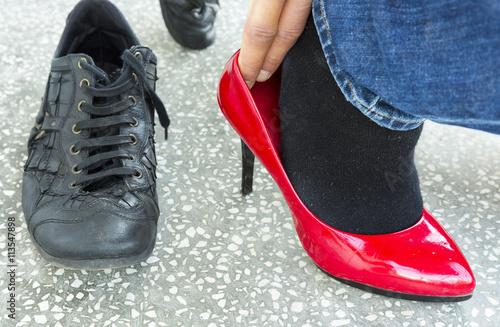Fotografia  Man putting on red ladies shoes