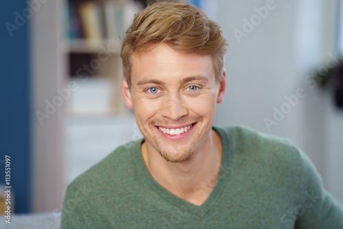 Fototapeta lächelnder junger mann in seiner wohnung obraz