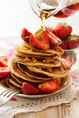 Fototapeta Pancakes with fresh strawberries, maple syrup and caramel topping