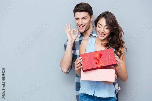 Photo  Young woman receiving gift from her boyfriend over gray background