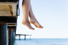 Woman's Feet Dangle From Jetty