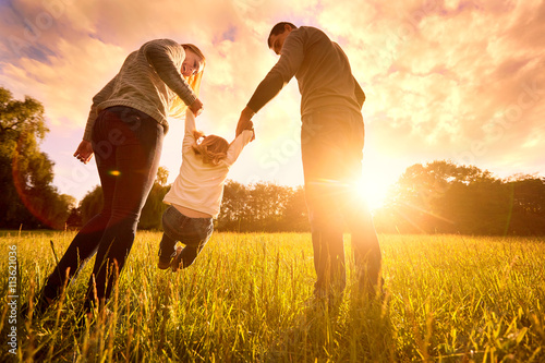 Fotografia  Parents hold the baby's hands.  Happy family in the park evening