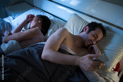 Sly boyfriend using mobile in bed while his girlfriend is sleepi Wallpaper Mural