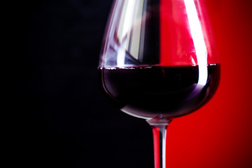 Fototapeta Wino glass of red wine is on the red background