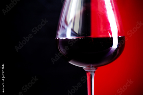 glass of red wine is on the red background - 113629846