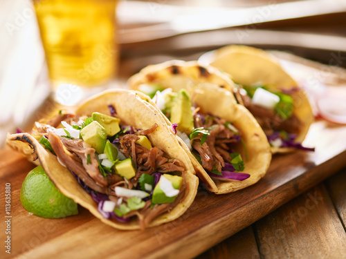 tasty mexican carnitas tacos with red cabbage, avocado, onion and cilantro